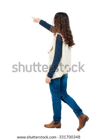 back view of walking  woman. beautiful redhead girl pointing.  backside view of person.  Rear view people collection. Isolated over white background. Girl in sheepskin jerkin goes and shows thumb. - stock photo