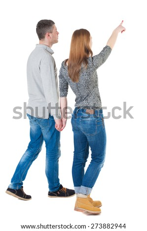 Back view of walking young couple (man and woman) pointing. Rear view people collection. backside view of person. Isolated over white background. girl holding hand of Man, and shows his hand forward. - stock photo