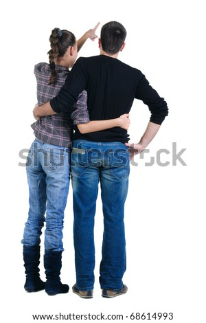 Back view of watching young couple pointing at wall. Rear view. Isolated over white background.