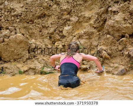 Back view of woman climbing up dirty wall from puddle.Unrecognizable - stock photo