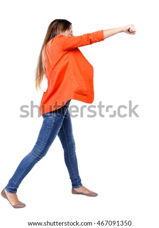 back view of woman funny fights waving his arms and legs. Rear view people collection. backside view of person.  Isolated over white background. girl in a red jacket stands sideways and strike his