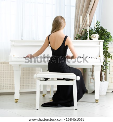 Back view of woman in black dress sitting and playing piano. Concept of music and arts - stock photo