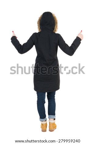 Back view of  woman  in parka thumbs up. Rear view people collection. backside view person. Isolated over white background. Girl in a black winter jacket with a hood with two hands showing thumbs up. - stock photo