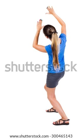 back view of woman  protects hands from what is falling from above.  Isolated over white background. Girl in a gray skirt and blue shirt covered his hands on top of something falling.