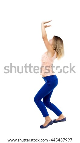 back view of woman  protects hands from what is falling from above. woMan holding a heavy load Rear view people collection. The blonde in a pink sweater holding something heavy on them.
