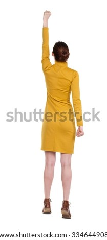 Back view of  woman.  Raised his fist up in victory sign.  Rear view people collection.  backside view of person.  Isolated over white background. Girl in  dress standing in a pose superhero.  - stock photo