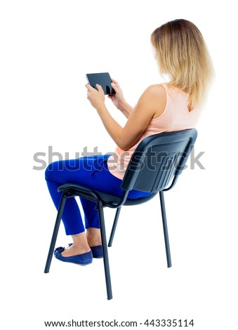 back view of woman sitting on chair and looks at screen of the tablet.  Rear view people collection.  backside view of person.. Blonde in blue pants sitting sideways on the office chair and plays game - stock photo