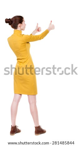 Back view of  woman thumbs up. Rear view people collection. backside view of person. Isolated over white background. Girl in mustard strict dress stands sideways and two hands showing thumb. - stock photo