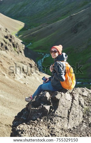 back view of woman traveler on a walk in the Valley of the river of Hveragerdi Iceland. Hiking Tour of Reykjadalur Hot Springs. woman sits on the cliff and use smartphone
