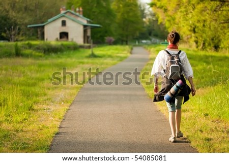 back view of woman walking on country road at springtime in France - stock photo