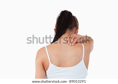 Back view of woman with pain in her neck against a white background - stock photo
