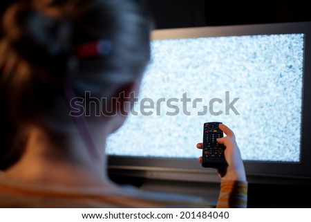 Back view of woman with remote control in front of TV set with noise on the screen - stock photo