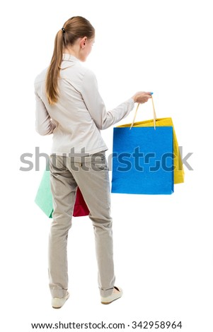 back view of woman with shopping bags . beautiful brunette girl in motion.  backside view of person.  Isolated over white background. Girl in gray jeans holding at arm's length paper bags. - stock photo