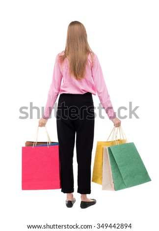 back view of woman with shopping bags . beautiful brunette girl in motion.  backside view of person. Isolated over white background. The girl in the pink shirt is held in both hands with shopping bags - stock photo