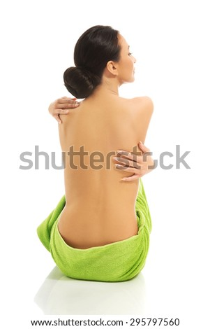 Back view of woman wrapped in green towel