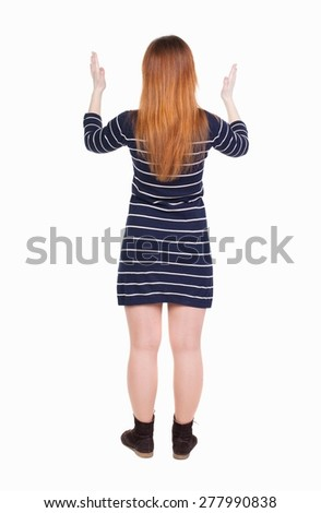 back view of woman. Young woman in vest presses down on something. Isolated over white background.  backside view of person. she holds his hand open, palm forward/ She spread her arms out. - stock photo