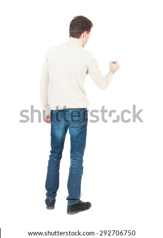 back view of writing man. Young man in jeans draws. Rear view people collection.  backside view of person. Isolated over white background.  The guy in white sweater draws felt-tip pen on the wall. - stock photo