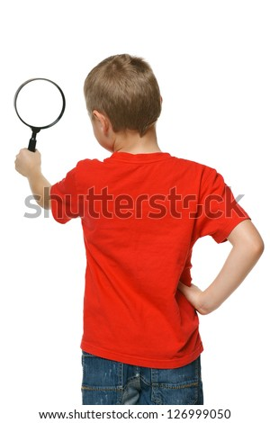 Back view of 6 years boy looking through the magnifying glass over white background - stock photo