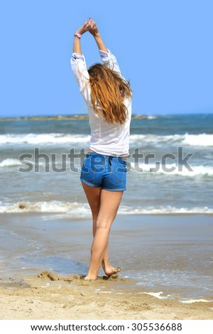 back view of young attractive woman in shorts and shirt playing on beach with sea in front in relax and freedom concept - stock photo