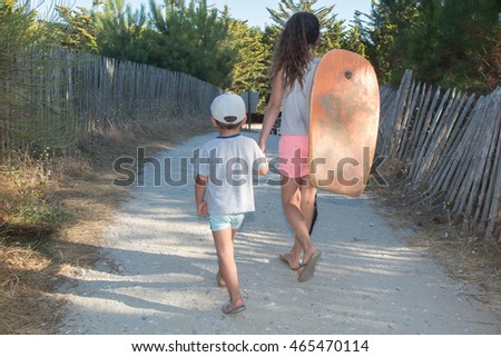 Back view of young beautiful girl and her brother walking at beach.