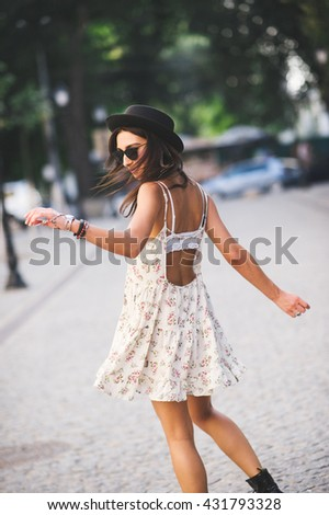 Back view of young beautiful girl in a summer dress dancing on street. Carefree hipster woman wearing hat and sunglasses feeling happy - stock photo