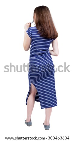 back view of young beautiful girl standing in thoughtful pose. Rear view people collection.   Isolated over white background. Girl in a blue striped dress with a felt-tip pen is thoughtfully. - stock photo
