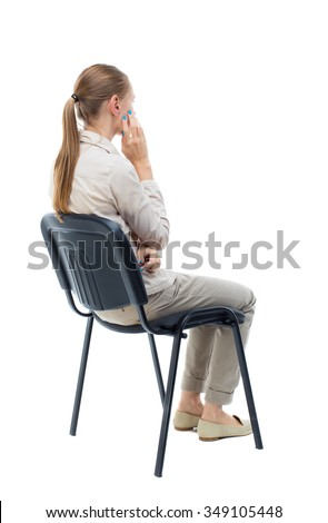 back view of young beautiful  woman sitting on chair.  girl  watching.   Isolated over white. Girl with long hair in a white jacket is sitting on a chair resting his hand on the cheek. - stock photo