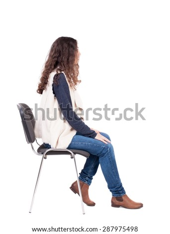 back view of young beautiful  woman sitting on chair.  girl  watching. Rear view people collection.   girl in a white tank top sitting on a stool and looking to the right. - stock photo