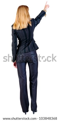 Back view of young blonde business woman pointing at wall. beautiful girl in dark suit. Rear view people collection. backside view of person. Isolated over white background. - stock photo