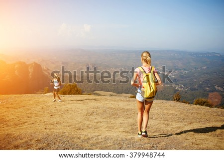 Back view of young blonde woman standing on a mountain hill and waiting her friend which standing below, two active male and female person hiking together with rucksacks in sunny summer day outdoors - stock photo