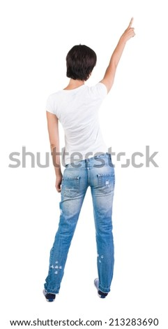 Back view of young brunette woman pointing at wall. beautiful girl. Rear view people collection. backside view of person. Isolated over white background.