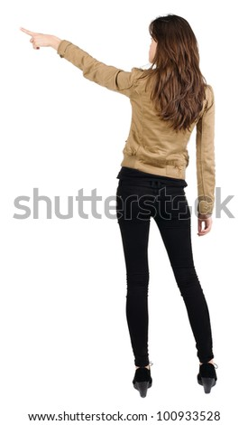 Back view of young brunette woman pointing  . beautiful girl in jacket showing gesture. Isolated over white background. Rear view. - stock photo
