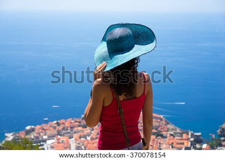 Back view of young brunette woman tourist in wide brim blue hat looking on Dubrovnik view from high mountain. - stock photo