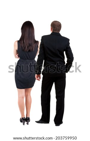 Back view of young business couple  look into the distance. beautiful friendly girl and guy together. Rear view. Isolated over white background. young woman holds the hand of her husband looking away - stock photo