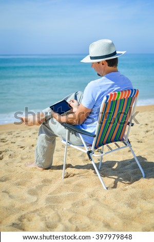Back view of young business man using tablet computer at tropical beach blue sky background. Mockup top view concept - stock photo