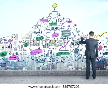 Back view of young businessman drawing abstract business sketch while standing on concrete rooftop. Success concept