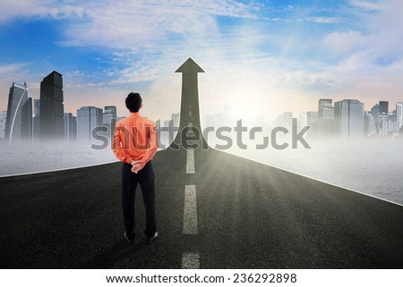 Back view of young businessperson standing on the highway going up as an arrow, symbolizing business growth and improvement - stock photo