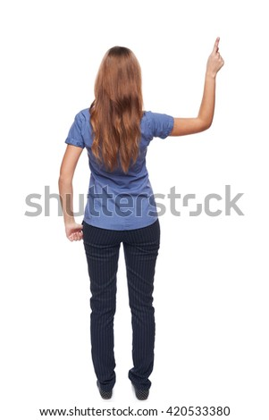 Back view of young casual female in full length pointing at blank copy space, isolated on white - stock photo