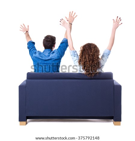 back view of young cheerful couple sitting on sofa isolated on white background - stock photo
