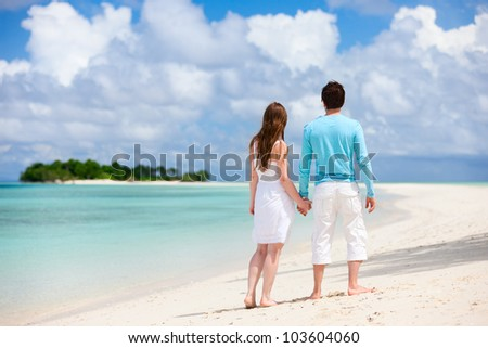 Back view of young couple at tropical beach - stock photo