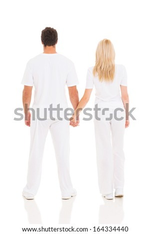 back view of young couple holding hands on white background - stock photo