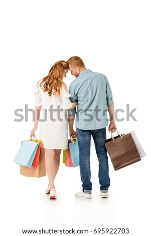 back view of young couple holding shopping bags and walking together isolated on white