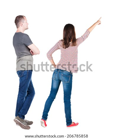 Back view of young couple  hug and look into the distance. beautiful friendly girl and guy together. Rear view. Isolated over white background. young woman holds the hand of her husband looking away - stock photo