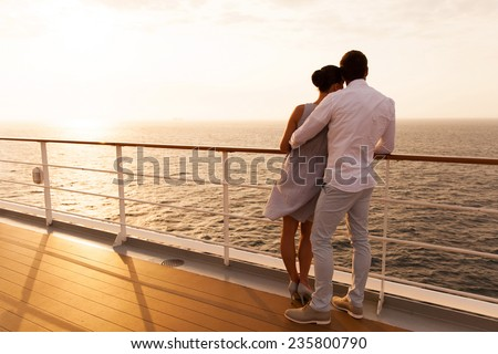 back view of young couple hugging at sunset on cruise ship - stock photo