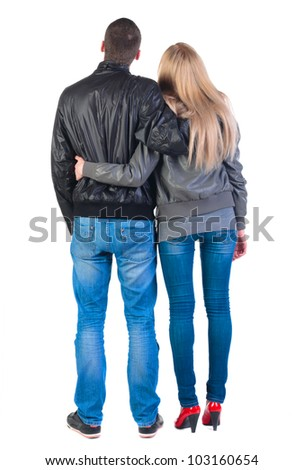 Back view of young couple (man and woman) hug and look into the distance. beautiful friendly girl and guy in jacket and jeans together. Rear view. Isolated over white background. - stock photo
