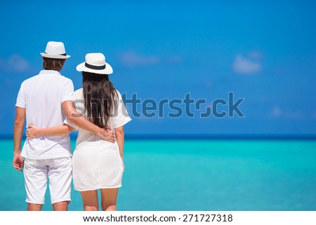 Back view of young couple on white beach at summer vacation - stock photo