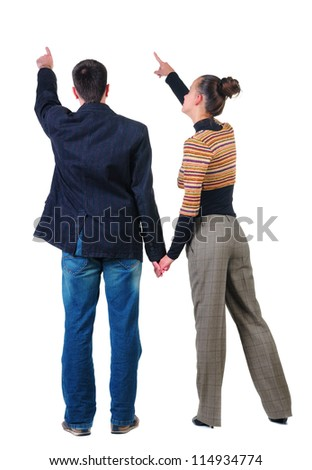 Back view of young couple pointing at wall. Rear view people collection.  backside view of person.  Isolated over white background. - stock photo