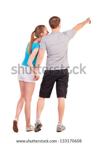 Back view of young couple pointing (woman and man). Rear view people collection.   backside view of person.  Isolated over white background. couple considering something, pointing at it with his hands - stock photo