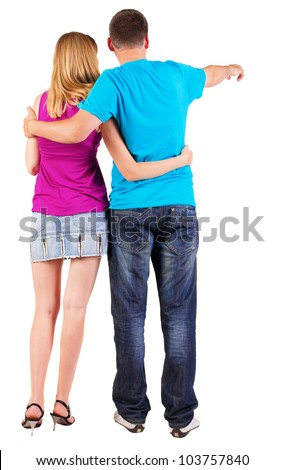 Back view of young couple pointing (woman, man). guy in jeansand girl in dress. looking into the distance. Rear view people collection. backside view of person. Isolated over white background. - stock photo
