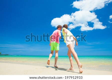 back view of young couple running at beach